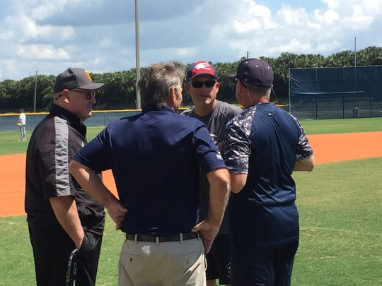 Estero baseball coach and new athletic director Gary White talks things over with his coaching staff before Monday's practice. White recently became the school's fifth athletic director in three years, but the 1991 Estero graduate and longtime coach hopes to bring needed stability to the position.