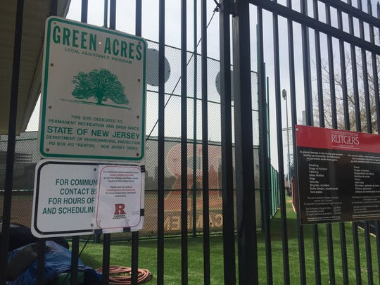 A temporary sign attached to permanent signage at Rutgers' athletic fields includes an updated phone number to call for public access.