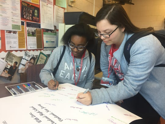 "Kyaira Mitchell (left) and Amaris Sotomayor add their names to the ""Sunrise Over Parkland"" poem that Vineland High School poets are sending to Marjory Stoneman Douglas High School."