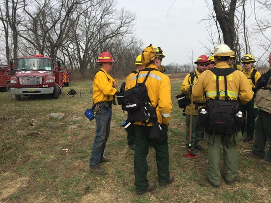 Firefighters with the state Forest Fire Service assemble in early April before conducting a prescribed burn to reduce the chance of wildfire in a field in  Warren County.