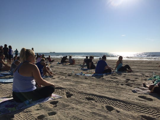 Greet the new day by practicing yoga on the beach.