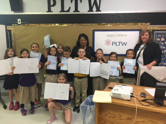 School coordinator Liz Mikitarian, right, and principal Charlene Montford, middle, with a group of kids in the school's Project Lead the Way classroom. One of the school district's accusations claims that Legacy Charter School has not fully implemented the Project Lead the Way curriculum.