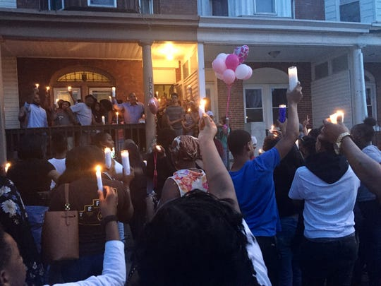 Community members hold candles at a vigil Saturday for Siryah Perez, a 5-year-old Camden girl who was fatally struck by a vehicle one day earlier.