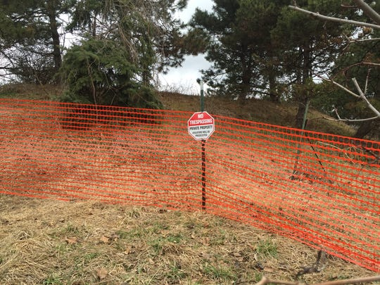 An orange fence warns people not to trespass. Inside