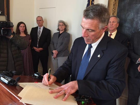 Gov. Phil Scott signs an executive order on Thursday,