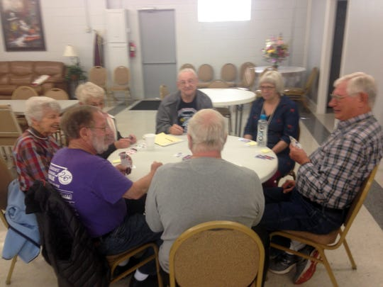 A group of seniors play the Phase 10 card game Thursday
