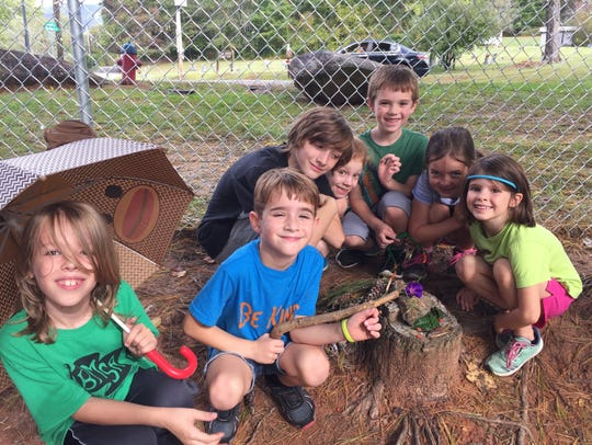 Kids from the Art in the Afternoon program build a small structure out of natural materials.
