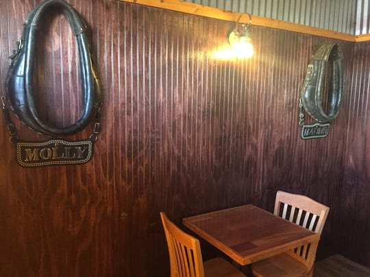 Two mule collars that once belonged to restaurant owner Scott Thomas's mules Molly and Maude carry a lot of sentimental value. Hanging them in his new Hotel Hickman Chuckwagon BBQ locatoin in Hamburg Township, Wednesday, April 25, 2018, shortly before the restaurant opened in May 2018 was a special moment for the cowboy history buff.