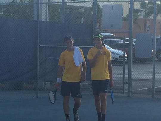 Naples' No. 1 doubles team of Michael Moll, left, and Justin Braverman, discuss strategy between the second and third sets of their regional championship match with Venice. Moll and Braverman pulled out the tiebreaker, clinching a 4-3 win for the Golden Eagles and a spot in the state team tournament.