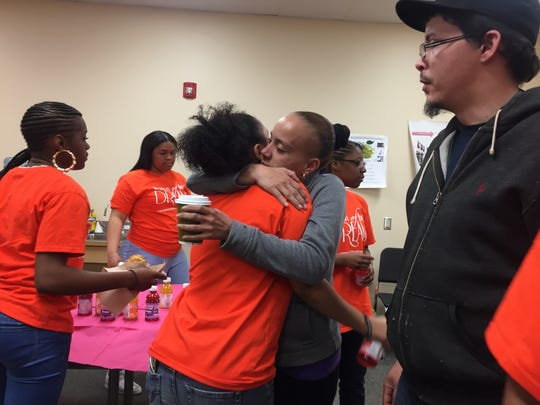 Trinity Martinez gets a hug from her mother before leaving for a weekend trip to Boston as her father looks on.