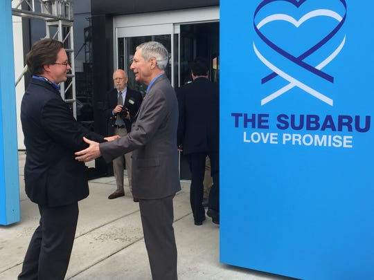 Tom Doll,Subaru of America CEO, greets a visitor to the company's new Camden headquarters Friday.