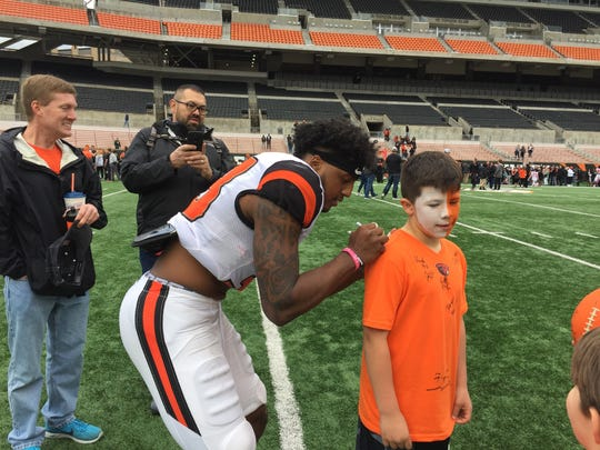 Oregon State safety Jalen Moore signs an autograph after the spring game at Reser Stadium on April 28, 2018.