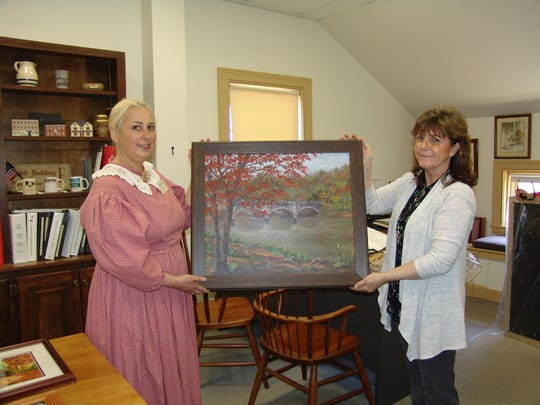 Stacie Stein and Lynda Daniel hold a bridge painting