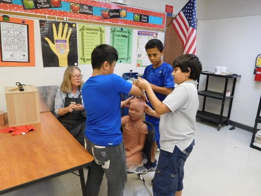 636607667686012942-Meale-looks-on-while-Conley-students-add-hair-to-the-little-girl-sculpture.JPG