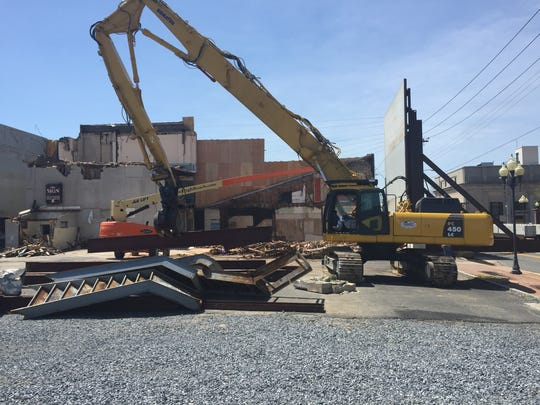 A steel beam is pulled from a halfway demolished building