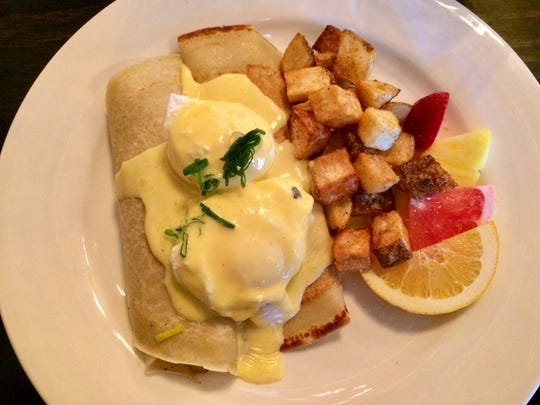 Crab crepe Benedict features blue crab, leeks, mushrooms with poached eggs topped with a hollandaise sauce, served with potato hash.