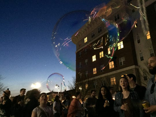 Soap bubbles float through the crowd Saturday, May 5, during the Waking Windows festival in Winooski.