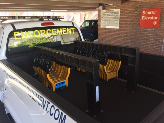 A parking enforcement truck  loaded with boots sits