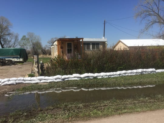 Sandbags are stacked in front of a home along the Sun