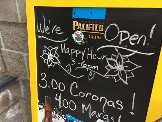 A happy hour sign at Tecate Grill.