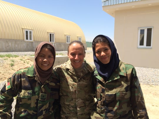 Leigh Ann Hester stands with two Afghan women in Afghanistan