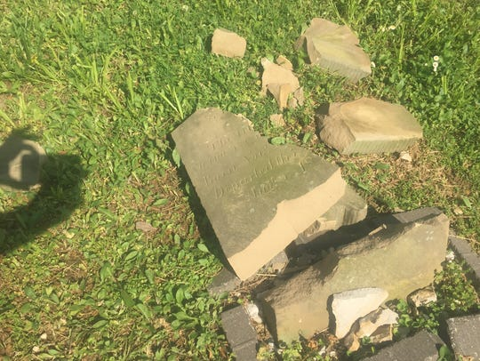 A gravestone in the Gen. Samuel Hopkins Cemetery lies shattered on Wednesday.