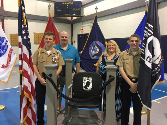 Cadet Evan Fallon (far right) built the stand on which sits the Delaware Military Academy's the Chair of Honor, which is always left empty to remember POW-MIA soldiers.