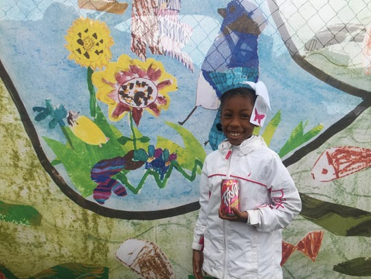 Kamiya Johnson, 9, stands next to a mural she and her