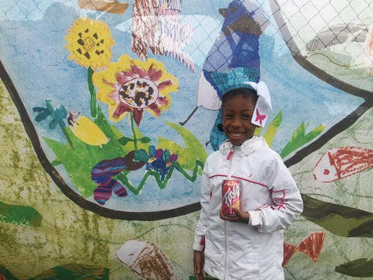 Kamiya Johnson, 9, stands next to a mural she and her third grade classmates at Thomas H. Dudley Family School created.