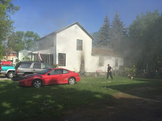 Smoke is seen coming from a home on Pine Street in