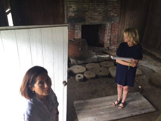 Monika Bridgforth, left, and Laura Vaughan of the Barrier Islands Center in Machipongo, Virginia show a visitor the interior of a 1700s quarter kitchen on the museum grounds. The building, which is in need of major repairs, is slated to be rehabilitated starting in fall 2018, and will be used for food-related exhibits and demonstrations.