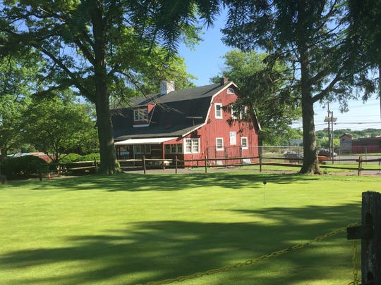 A clubhouse rises above a sun-dappled green at Golfland