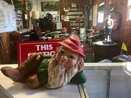 A reclining gnome is part of an eclectic display in