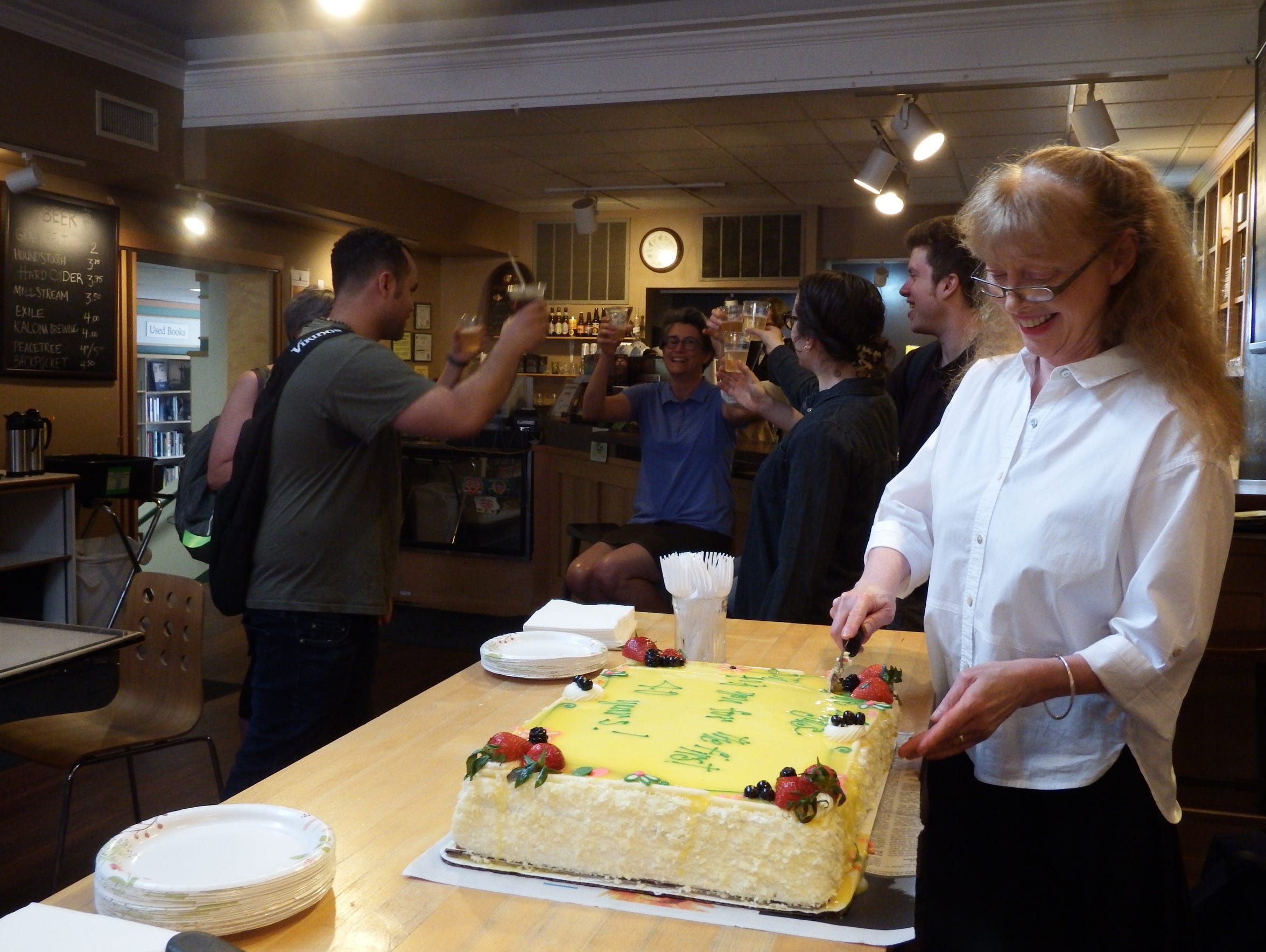 Prairie Lights co-owner Jan Weissmiller cuts a cake