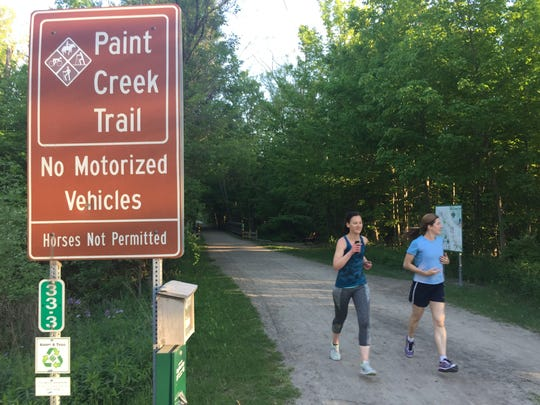 Runners north of Rochester in Oakland County's Paint Creek Trail pass one of many signs that prohibits motorized vehicles. Yet, a new state law over-rides that and classifies electric bicycles as non-motorized vehicles.