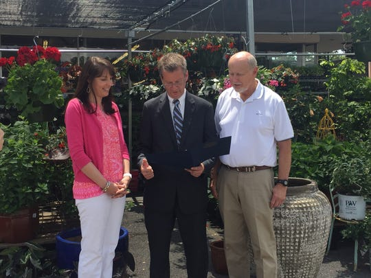 Elizabeth Mayo Cox and her father, firm president Claxton Mayo, receive a proclamation from County Mayor Tim Burchett during the 140th anniversary celebration of Mayo Garden Center in Bearden.