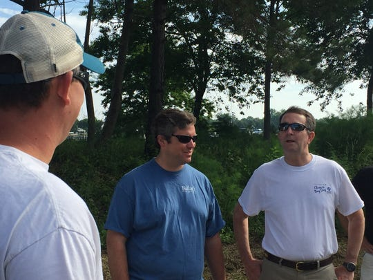 Gov. Ralph Northam, far right, chats with Chad Ballard, middle, and Clyde Cristman before the start of a Clean the Bay Day event in Cape Charles, Virginia on Saturday, June 2, 2018.
