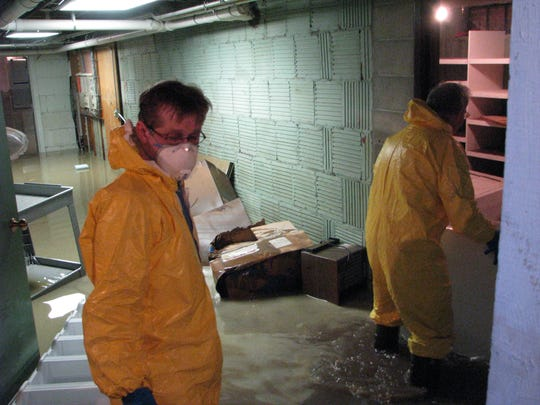 Tom O'Connor and Dr. Doug Kelly clean up the basement of the morgue after flooding in June. 2008.
