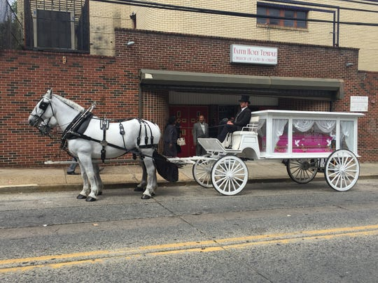 A horse-drawn carriage holds the coffin of Gabby Hill-Carter, an 8-year-old murder victim in Camden in 2016.