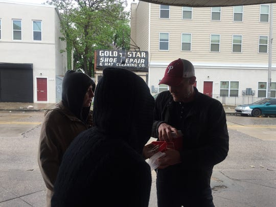 Jay Lassiter talks to two women on Broadway in Camden about using clean needles.