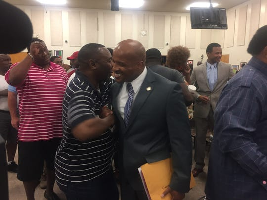Former football coach Teli White, on right, greets supporters after the hearing on his termination in front of the school board Wednesday June 6.