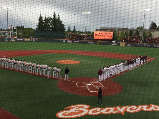 Oregon State and Minnesta players stand for the National