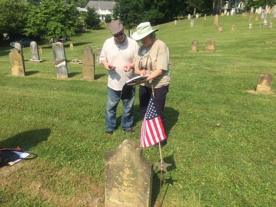 Steve Kelly and Lyn Boone consult graveyard records to confirm the grave location of one of his ancestors buried in Old Colony.