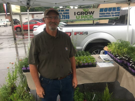 """Tom Becker of """"I Grow U Pick"""" said he was having a fair number of shoppers drop by June 8, despite a fairly steady rain throughout the market's duration that Friday."""