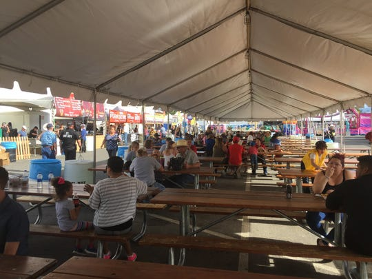 A long tent shelters ranks of family-style tables at the Reno Rodeo food court.