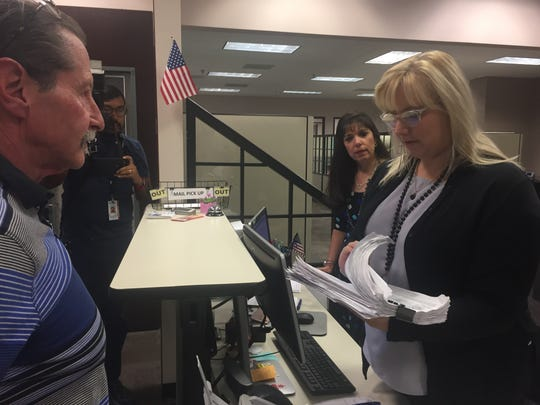 Open space advocate Rick Bonart submits a petition to City Clerk Darby Winters on June 20. The petition seeks to protect open land near the Franklin Mountains State Park from development.