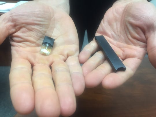 A detail image of a JUUL device and flavor pod confiscated