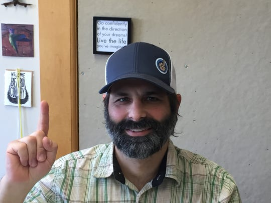 Brando Rich holds up one finger - the traditional sign of a Phish or Grateful Dead fan in search of a concert ticket - at the CashorTrade office in Burlington on June 26, 2018.