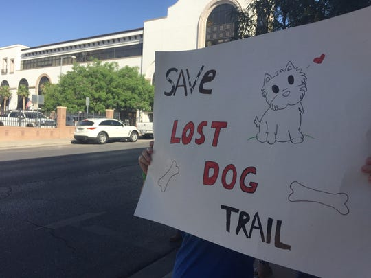"An open space advocate holds a sign that says, ""Save Lost Dog Trail,"" in June in front of City Hall."