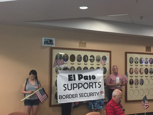 "A small group holds up a sign that reads ""El Paso supports border security"""